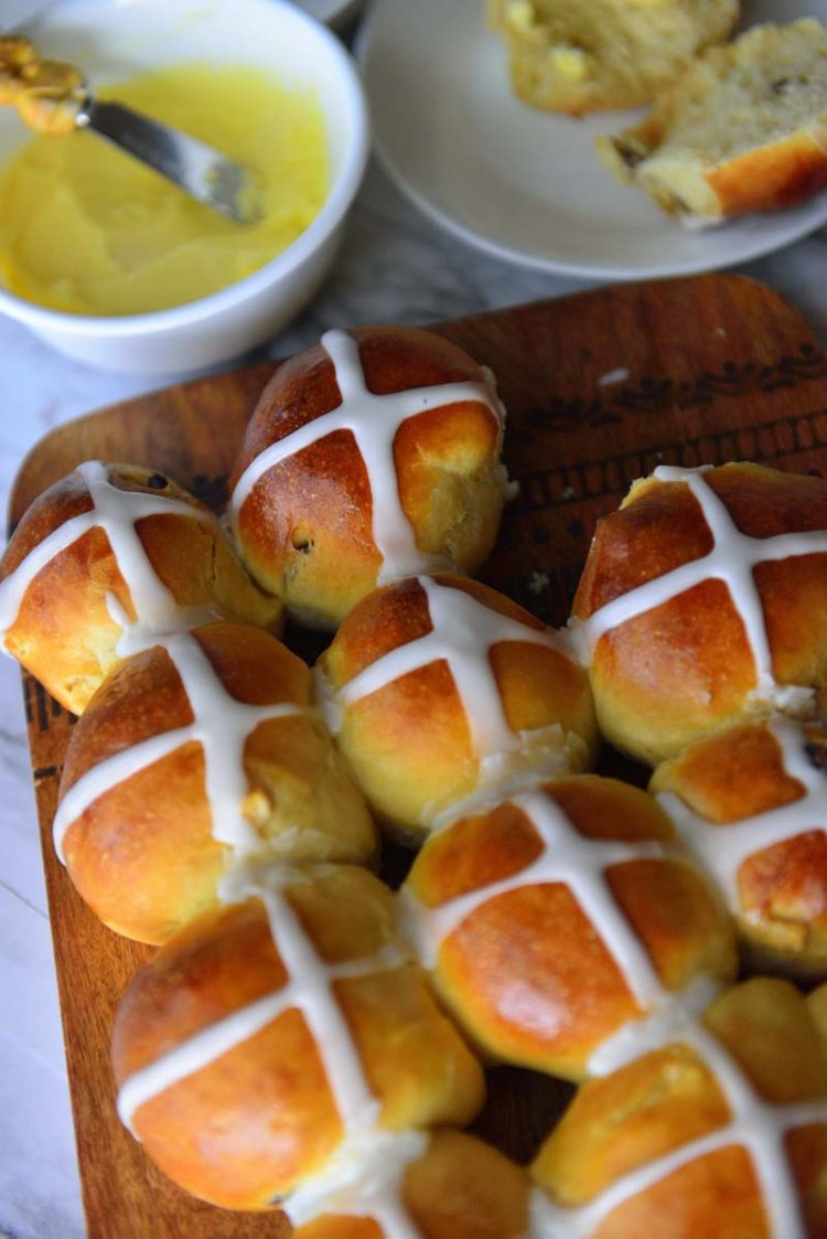 Hot Cross buns on a board with butter in a bowl next to it.