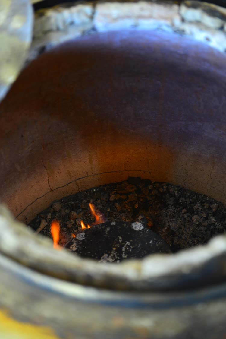 A hot tandoor with smoldering fire at the base