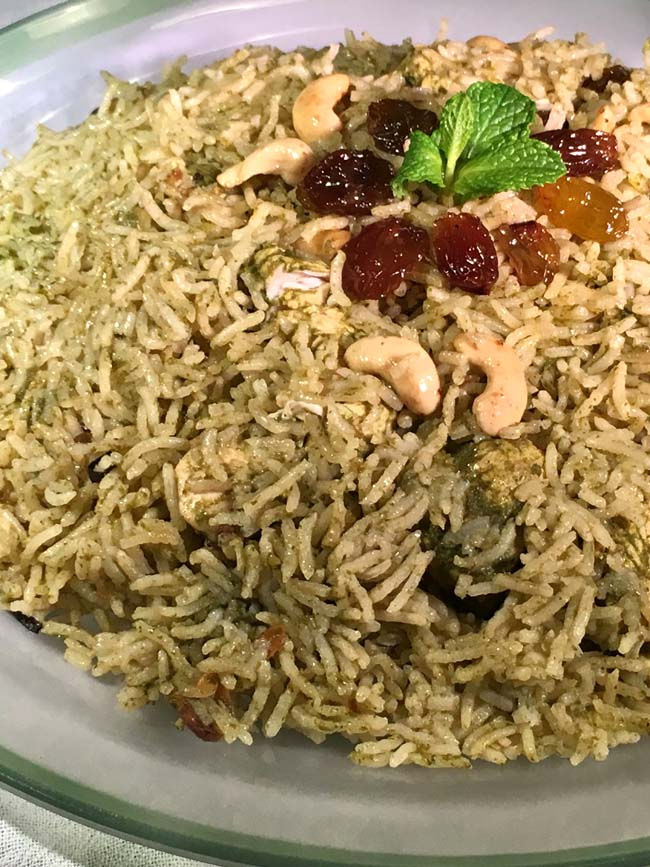 Green Chicken biriyani on a clear platter with green rim