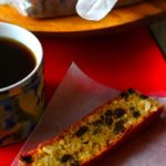 A slce of plum cake on a wax paper with a mug of coffee next to it. Caption - Easy Plum Cake