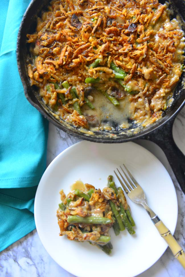 Green Bean Casserole in  a cast iron skillet  and a scoop of the same served on a white plate and a  fork.
