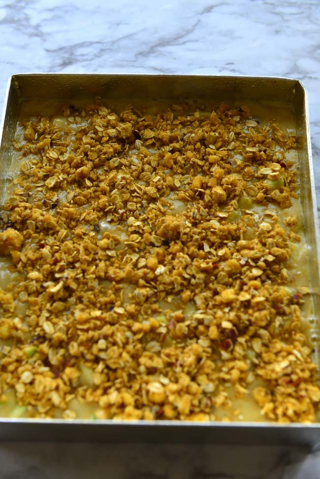 Cake batter spread in the pan with crunchy streusel topping, ready for the oven