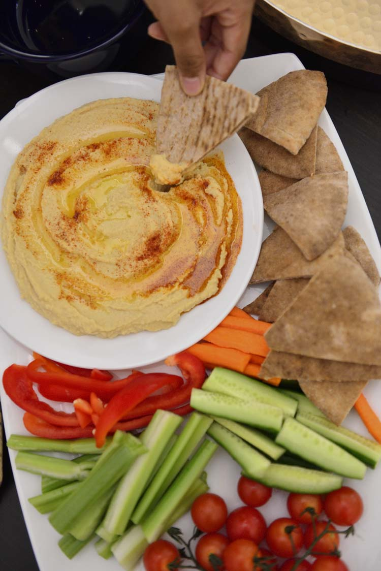 A plate of hummus  with slices of pita bread and vegetables around if.